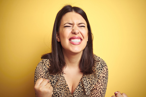 istock Young beautiful brunette woman wearing leopard shirt over yellow isolated background very happy and excited doing winner gesture with arms raised, smiling and screaming for success. Celebration concept. 1174444481