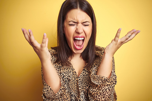 istock Young beautiful brunette woman wearing leopard shirt over yellow isolated background celebrating mad and crazy for success with arms raised and closed eyes screaming excited. Winner concept 1174444546