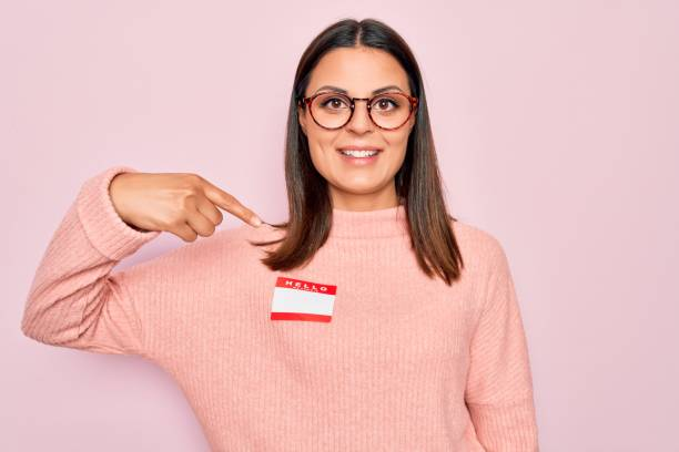 Young beautiful brunette woman wearing sticker with hello my name is message pointing finger to one self smiling happy and proud stock photo