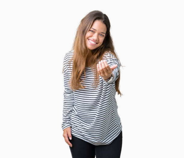 Young beautiful brunette woman wearing stripes sweater over isolated background Beckoning come here gesture with hand inviting happy and smiling stock photo