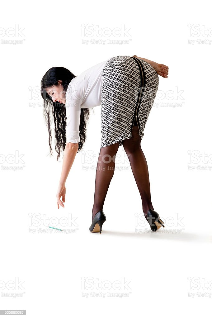 Young beautiful business woman bending down to pick up pencil stock photo
