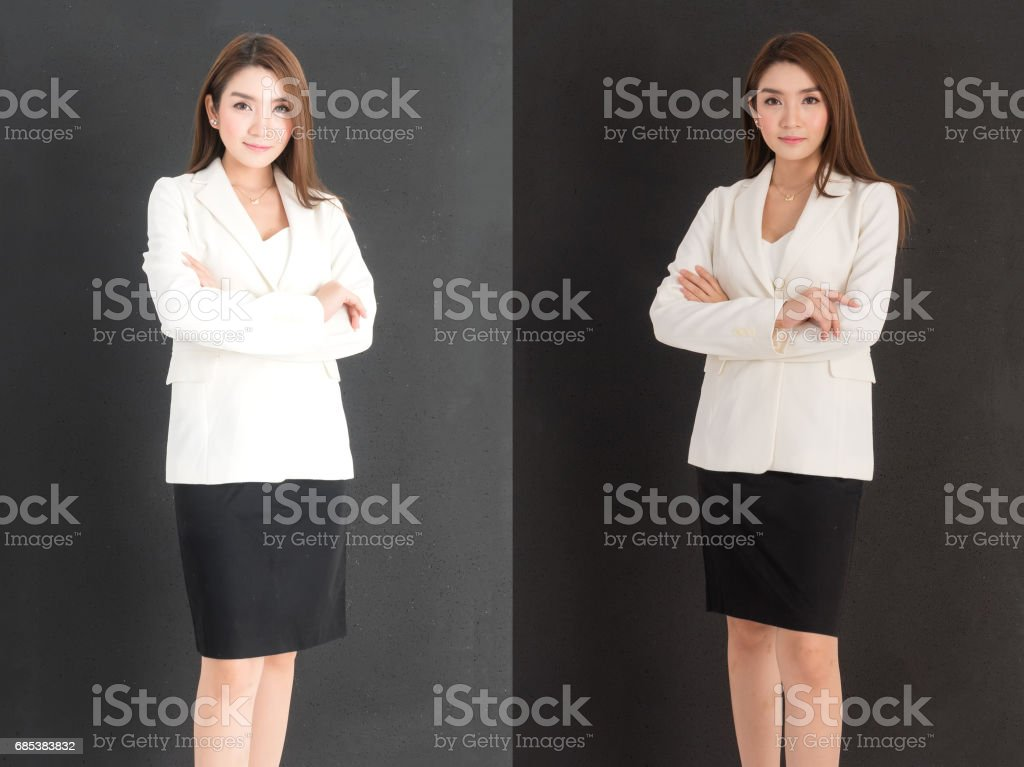 young beautiful business woman in white suit and black skirt standing with 2 acting (cross one arm) over black background foto de stock royalty-free