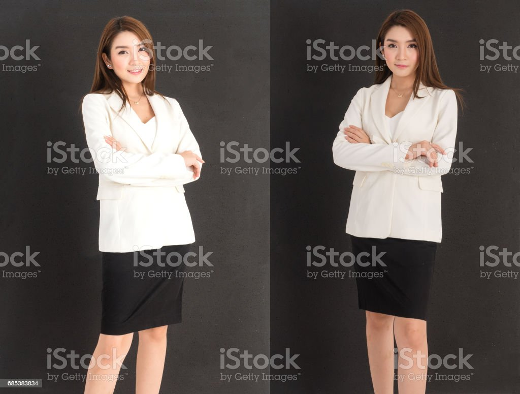 young beautiful business woman in white suit and black skirt standing with 2 acting (cross one arm) over black background royalty-free stock photo