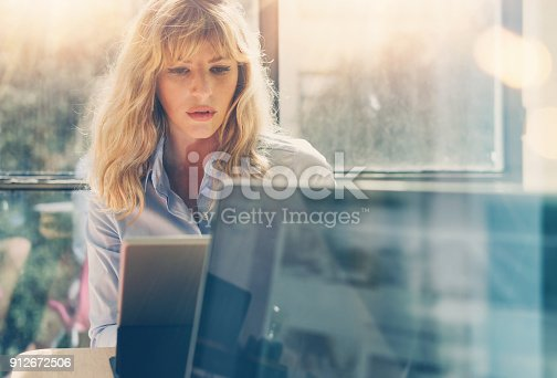 istock Young beautiful business woman working at laptop computer at sunny office.Panoramic windows on blurred background.Horizontal. 912672506