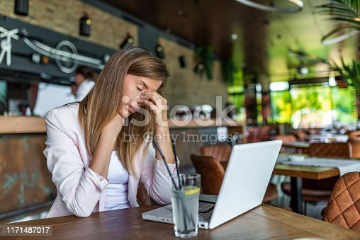 Young and beautiful businesswoman tired from work at coffee shop. Woman holding her head. Business women stressed and under pressure. Young beautiful businesswoman tired from work.
