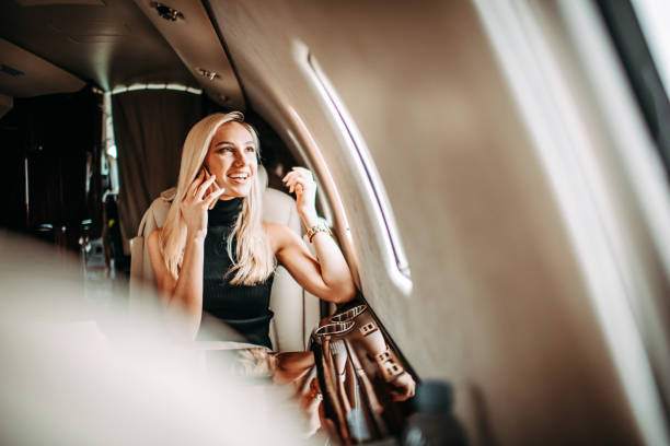 Young beautiful businesswoman traveling in a private jet and smiling while having a conversation on a smart phone stock photo