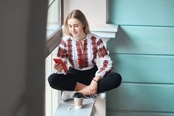 Young beautiful caucasian girl student wearing a vyshyvanka, a traditional Ukrainian embroidered shirt checks her smartphone at university - foto stock