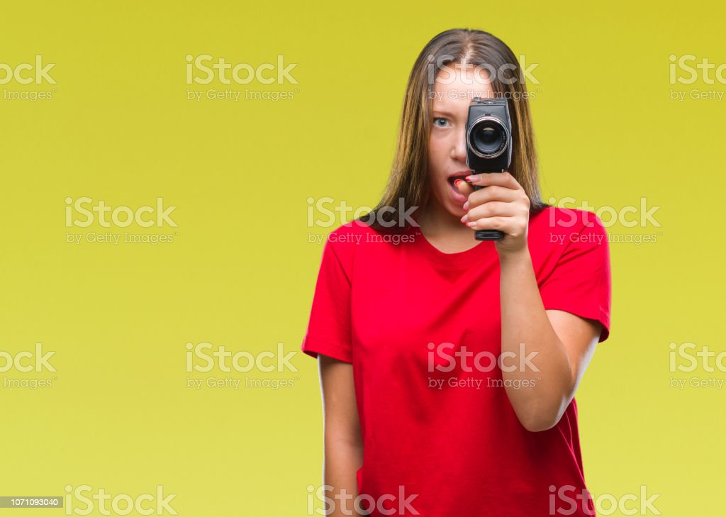 Young beautiful caucasian woman filming using vintage video camera...