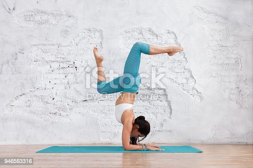 istock Young beautiful caucasian woman in yoga pose in studio on white brick wall background. Healthy life yoga concept. working out, wearing sportswear, white shirt, green pants 946563316
