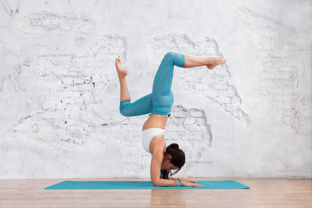 Young beautiful caucasian woman in yoga pose in studio on white brick wall background. Healthy life yoga concept. working out, wearing sportswear, white shirt, green pants stock photo