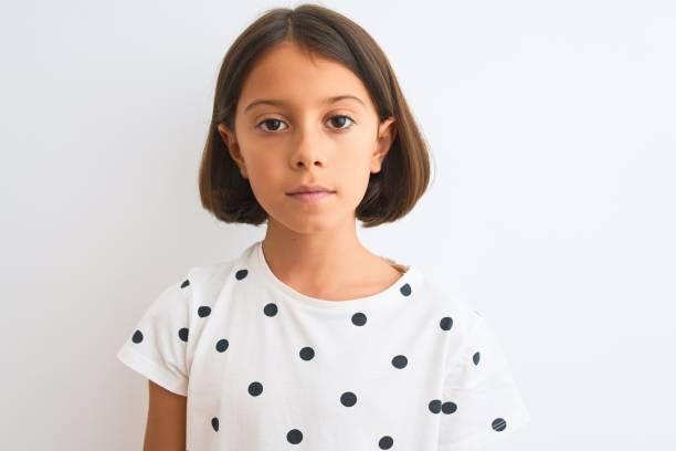 jonge mooie kind meisje dragen casual t-shirt staande over geïsoleerde witte achtergrond met een zelfverzekerde uitdrukking op slimme gezicht denken serieus - alleen één meisje stockfoto's en -beelden