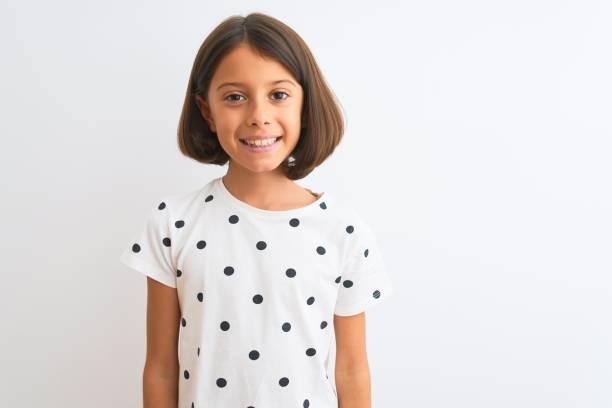 jonge mooie kind meisje dragen casual t-shirt staande over geïsoleerde witte achtergrond met een gelukkige en koele glimlach op gezicht. gelukkige persoon. - alleen één meisje stockfoto's en -beelden