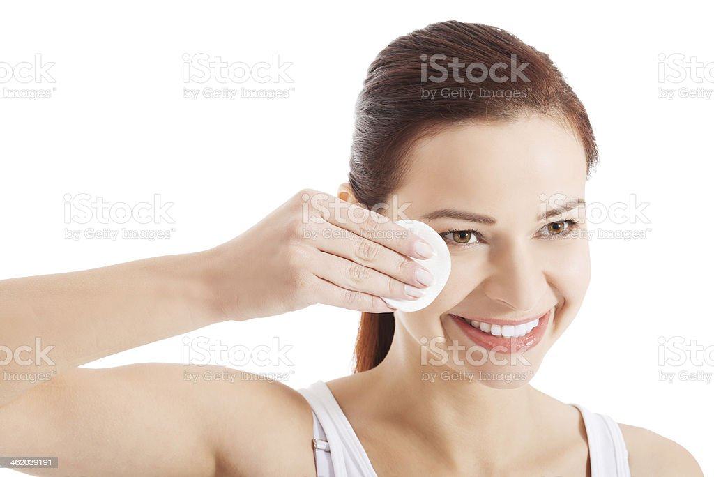Young beautiful cleaning face with cotton pads. stock photo