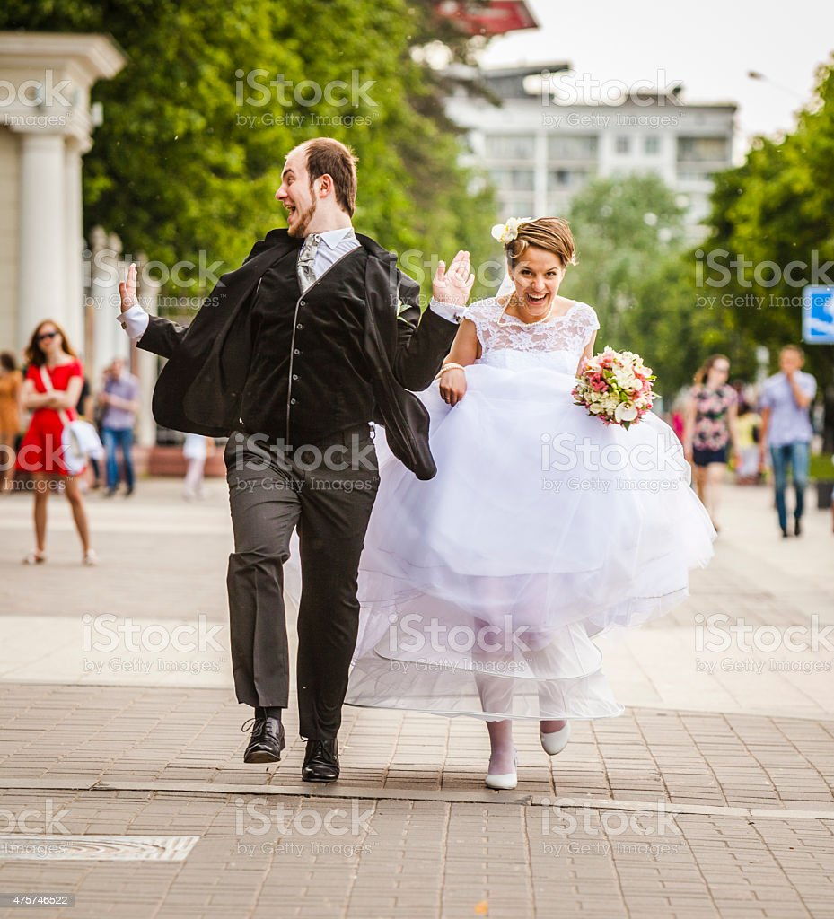 Young beautiful couple, bride and groom, running on the street stock photo