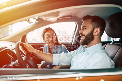 istock Young beautiful couple buying a new car in dealership 1017620358