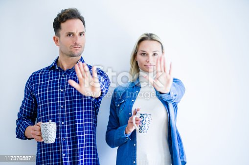 Young beautiful couple drinking cup of coffee standing over isolated white background with open hand doing stop sign with serious and confident expression, defense gesture
