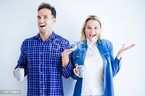 854381886 istock photo Young beautiful couple drinking cup of coffee standing over isolated white background very happy and excited, winner expression celebrating victory screaming with big smile and raised hands 1187188842