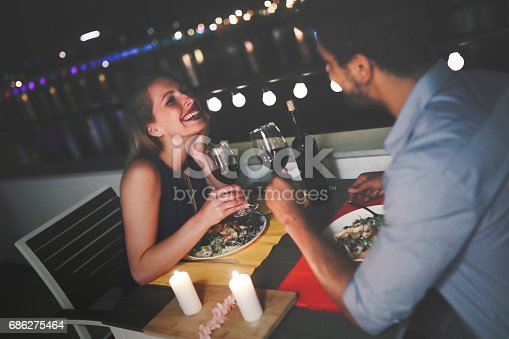 istock Young beautiful couple having romantic dinner on rooftop 686275464
