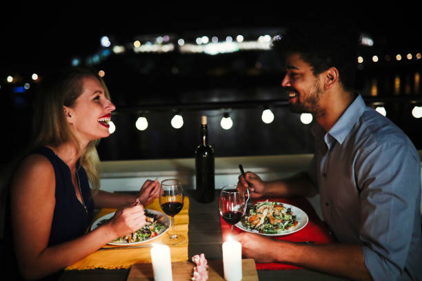 young beautiful couple having romantic dinner on rooftop - calendar date stock photos and pictures