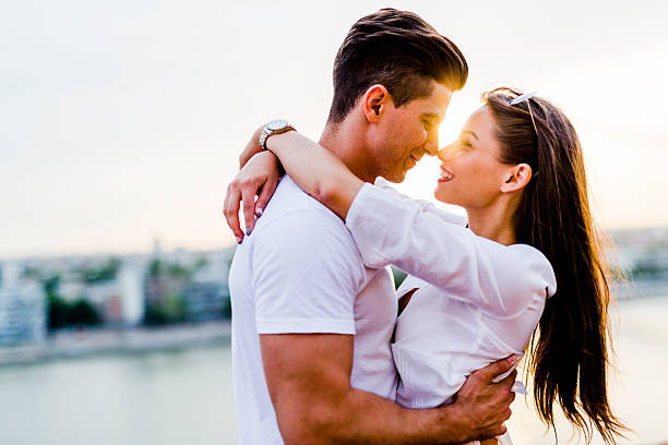 Young beautiful couple hugging and about to kiss stock photo