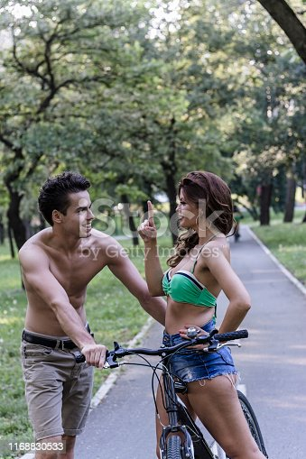1060280760 istock photo Young Beautiful Couple is Enjoying in Bicycle Ride on Sunny Day in Nature 1168830533