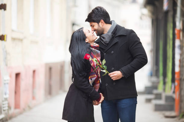 young beautiful couple kissing on the street - falling in love stock pictures, royalty-free photos & images