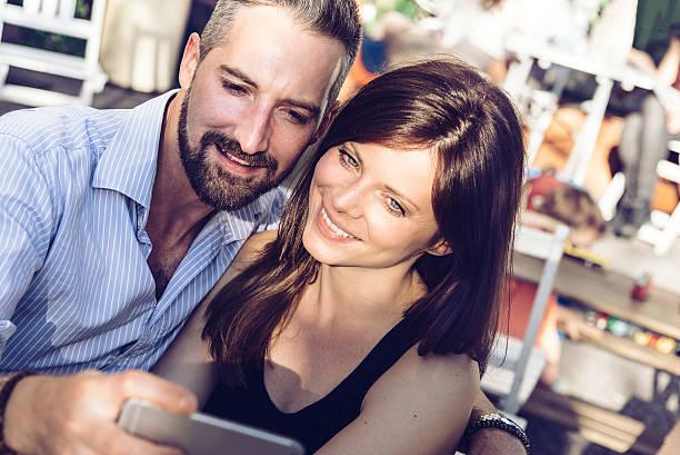 young beautiful couple looking at mobile phone  in summer light - kvinna cloes up bildbanksfoton och bilder