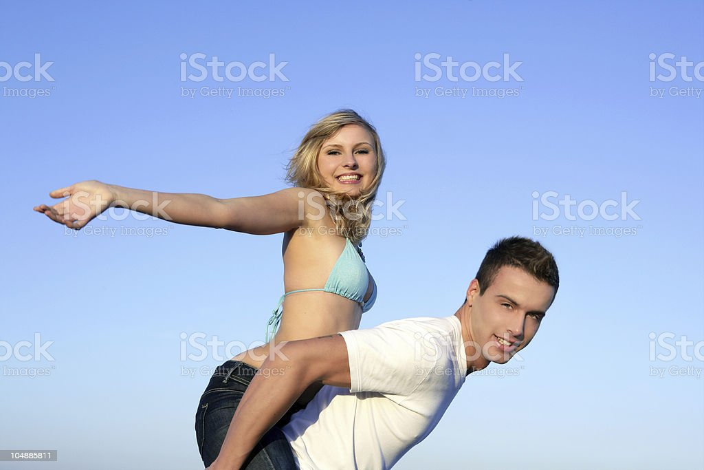 Young beautiful couple playing over blue sky royalty-free stock photo