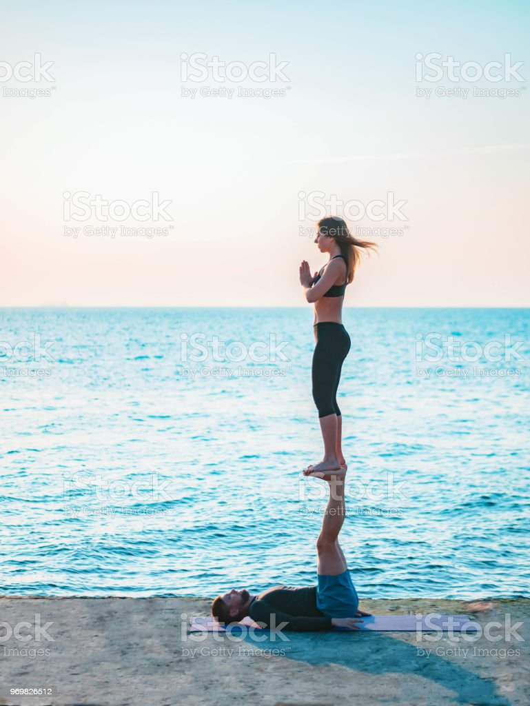 Young beautiful couple practicing acro yoga on the sea beach near water. Man and woman doing everyday practice outdoor on nature background. Healthy lifestyle concept stock photo