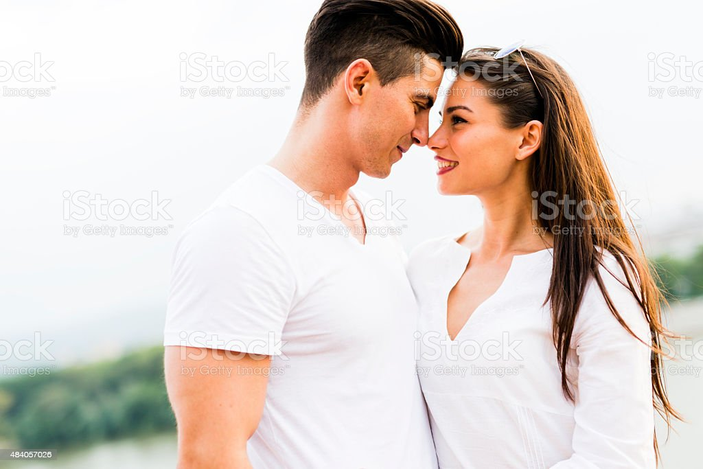 Young beautiful couple rubbing noses as a sign of love stock photo