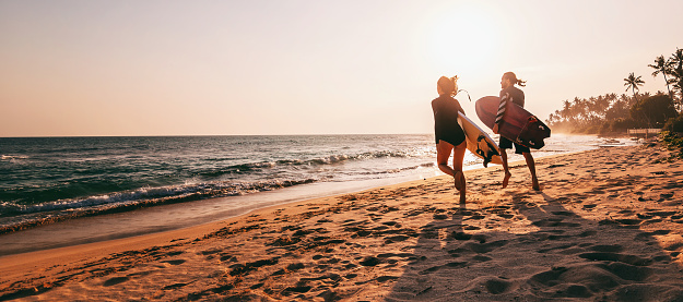 Young beautiful couple walking along the sandy beach near the ocean at sunset with surfboards, outdoor activities