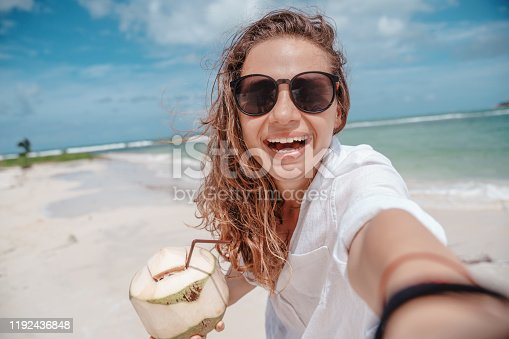 Young beautiful curly girl in a white shirt enjoys life with a coconut in her hands, makes selfie on a smartphone, travel and vacation on the tropical ocean.