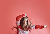 Young beautiful cute girl dancing on red background, modern slim hip-hop style teenage girl jumping.