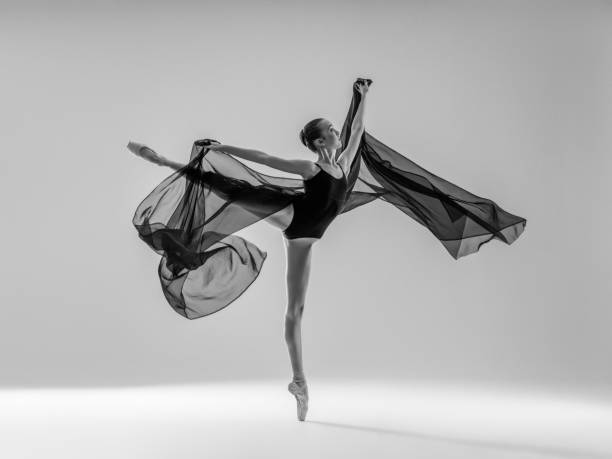 Young beautiful dancer dancing on gray background stock photo