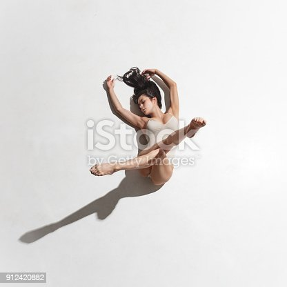 Young beautiful dancer in beige dress dancing on white studio background. Top view