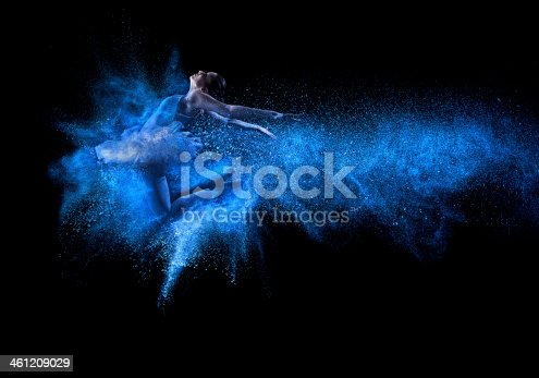 istock Young beautiful dancer jumping into blue powder cloud 461209029