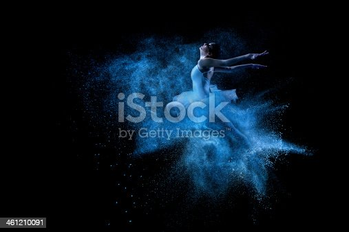 istock Young beautiful dancer jumping into blue powder cloud 461210091