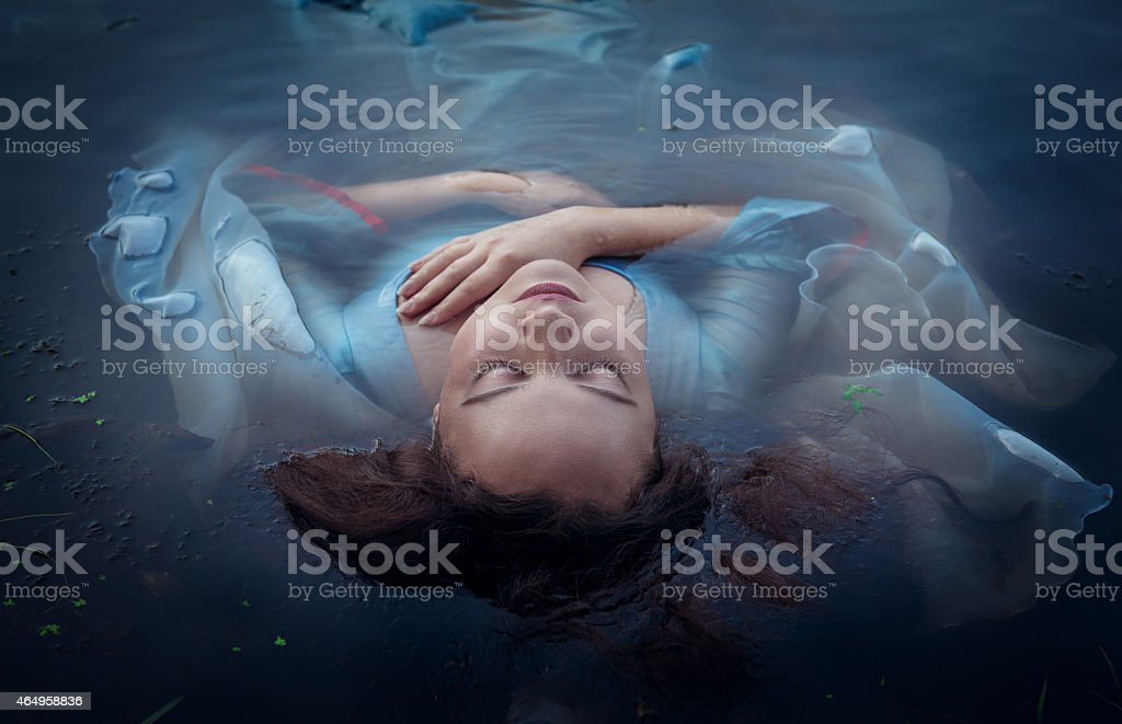 Young beautiful drowned woman lying in the water stock photo