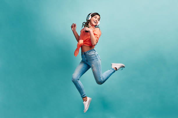 Young beautiful energy girl with white headphones listening to music laughs and jump on blue background in studio and looks away.Dressed in an orange shirt and light jeans, holding a phone. stock photo