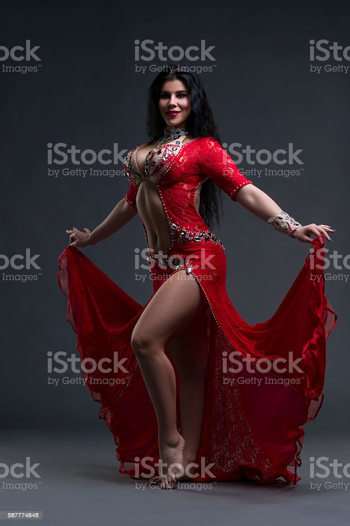 Young beautiful exotic women performs belly dance in red dress stock photo