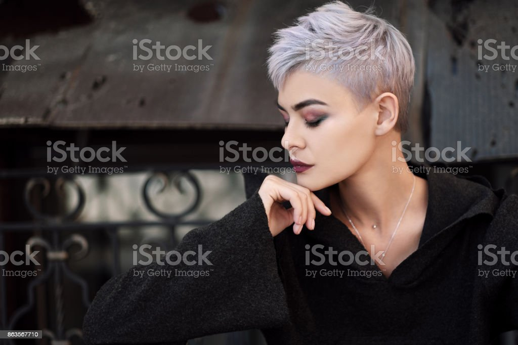 Young beautiful fashion girl shooting outdoors near brick wall at house stock photo