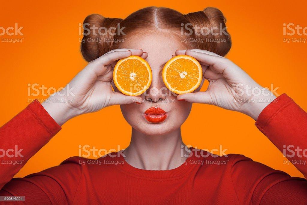 Young beautiful fashion model with orange. studio shot. stock photo