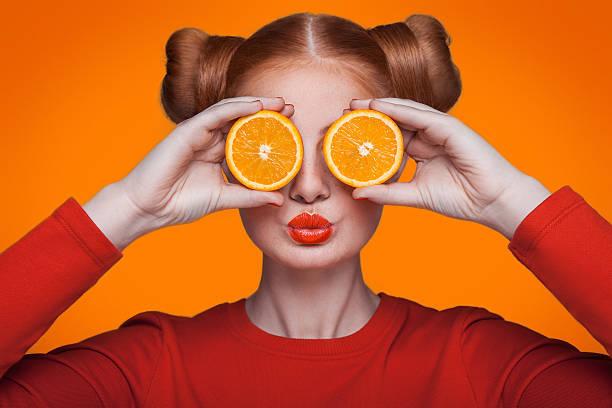Modelo de moda jovem bonito com laranja. Foto de estúdio. - foto de acervo