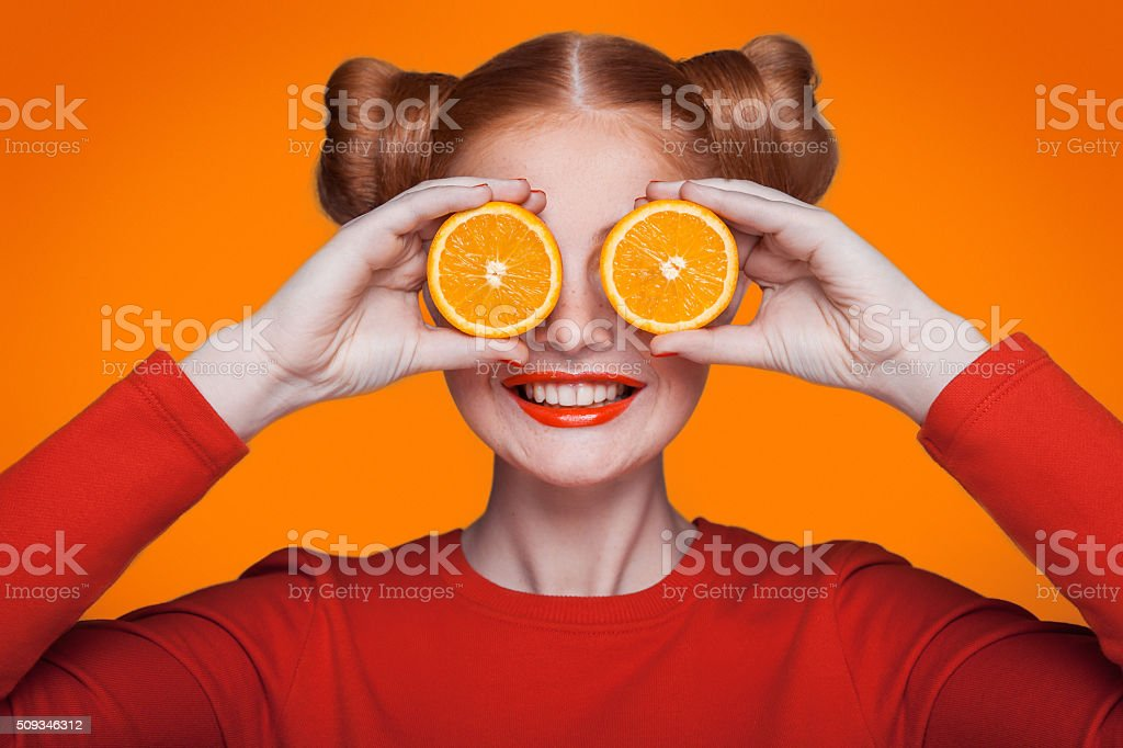 Young beautiful fashion model with orange. studio shot. stock photo