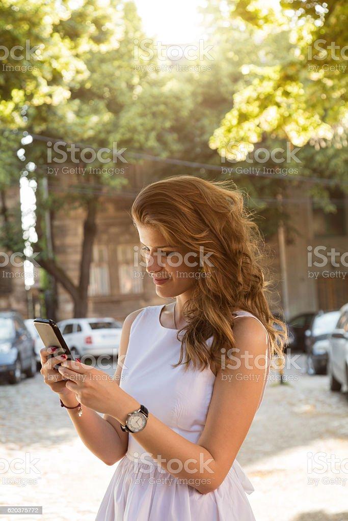 Młodego piękne modne Kobieta używająca telefon komórkowy na świeżym powietrzu. zbiór zdjęć royalty-free