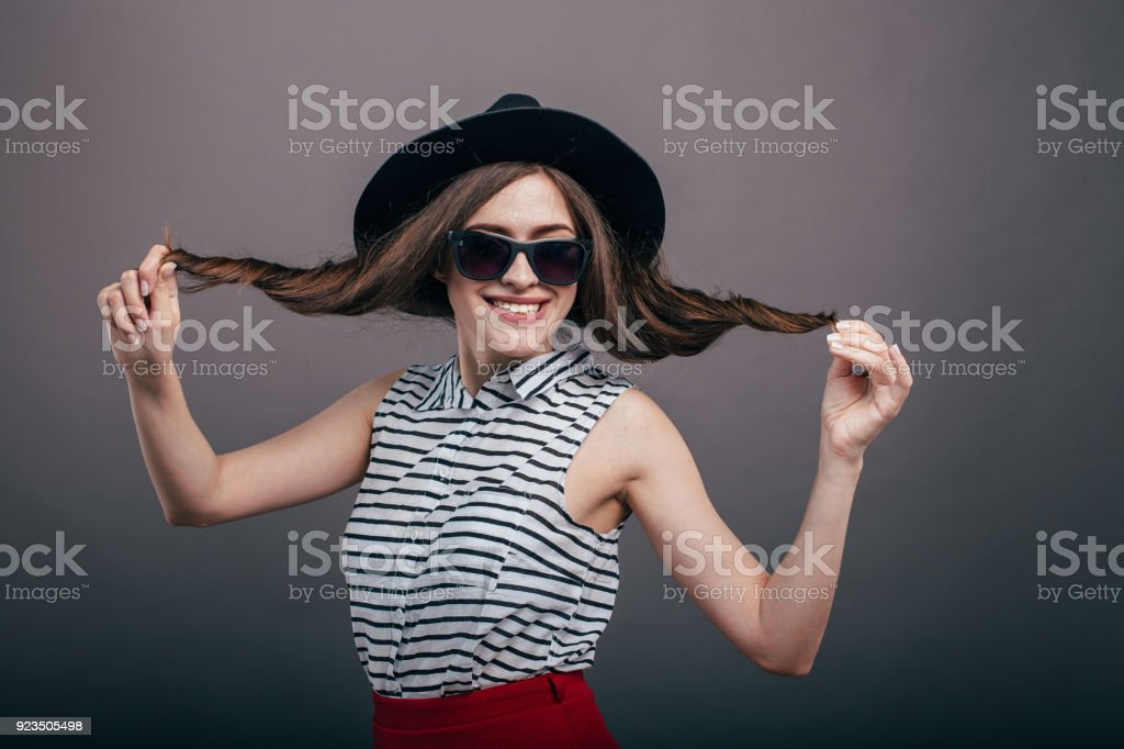 3b8adf926a8 Young beautiful fashionable woman with trendy makeup in black hat and  glasses on the grey background