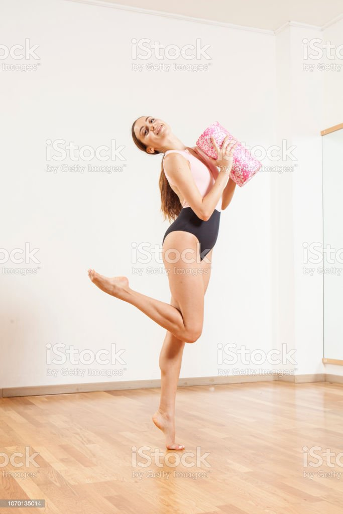Young beautiful female  ballett dancer posing with a foam roller stock photo