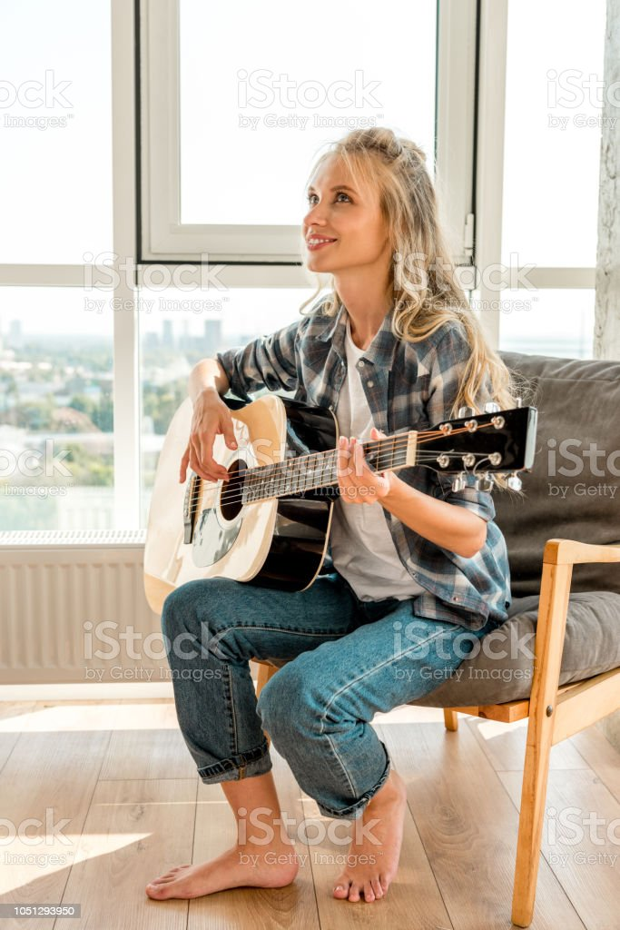 young beautiful female guitarist in casual clothing playing acoustic guitar at home stock photo