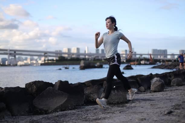 年輕的美麗的女性在海灘上奔跑圖像檔