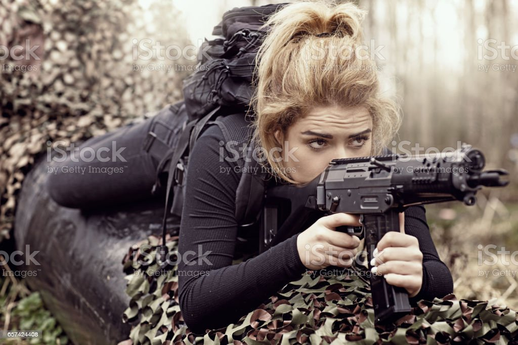 Young Beautiful Female Soldier in Military Shoot in woodlands stock photo